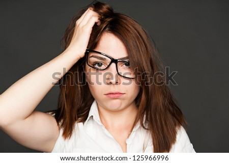 portrait of tired young woman in glasses over dark background - stock photo