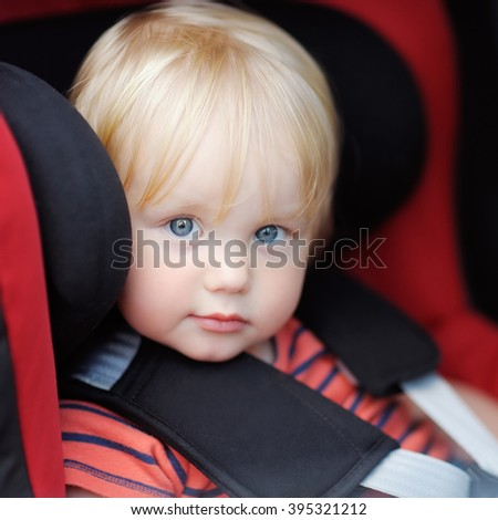 Portrait of toddler boy sitting in car seat - stock photo