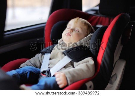Portrait of toddler boy sleeping in car seat - stock photo