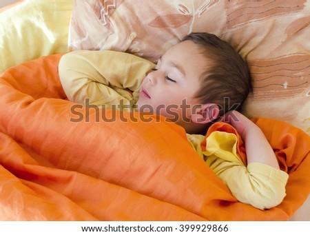 Portrait of toddler child  boy sleeping under an orange blanket in a bed. - stock photo