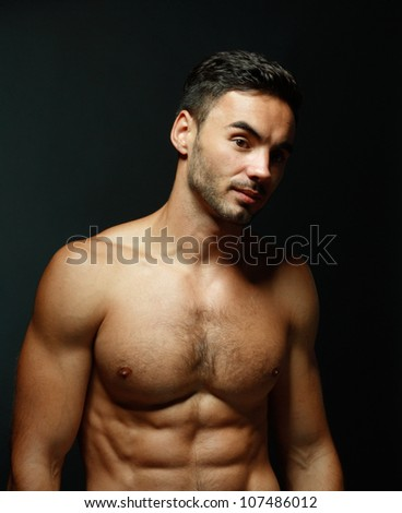 portrait of topless athletic macho man posing over black background - stock photo