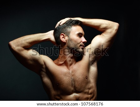 portrait of topless athletic man posing over black background - stock photo