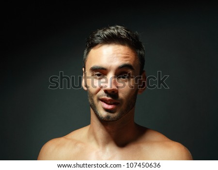 portrait of topless macho man raising his eyebrow and smiling over black background - stock photo