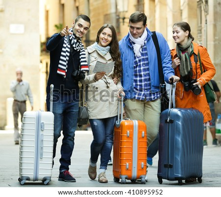 Portrait of tourists with map and baggage in European city - stock photo