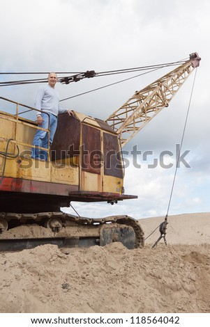 Portrait of tractor operator at sand pit - stock photo