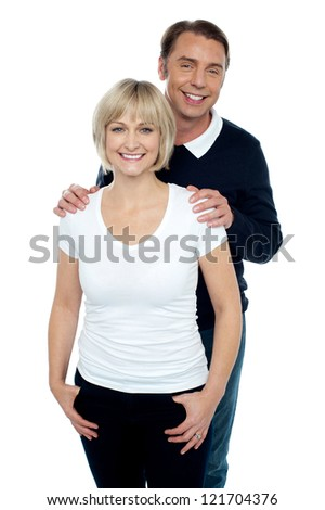 Portrait of trendy couple striking stylish pose. Man holding his wife from behind. - stock photo