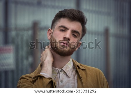 portrait of trendy looking young hipster man in industrial area