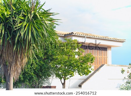 Portrait of tropical apartment building with trees. - stock photo
