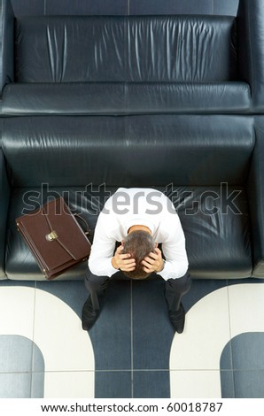 Portrait of troubled businessman touching head while sitting on sofa - stock photo