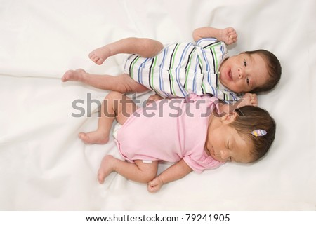 Portrait of twin babies boy and girl - stock photo