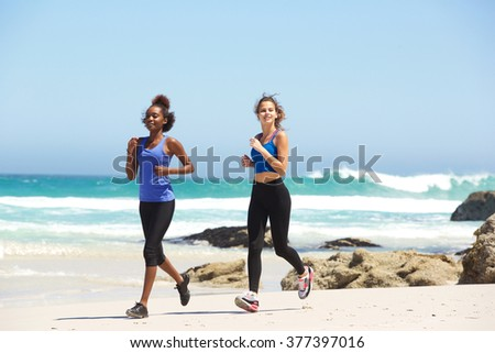 Portrait of two active young women running on the beach