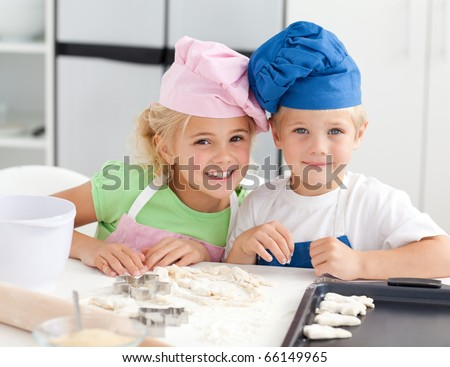 Portrait of two adorable children baking in the kitchen at home - stock photo