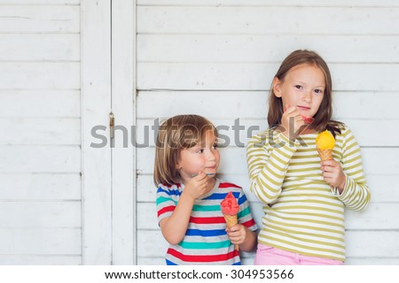 Portrait of two adorable kids eating colorful ice cream outdoors, standing next to white wooden background - stock photo