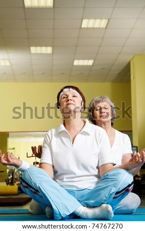 Portrait of two aged females doing yoga exercise in sport gym - stock photo