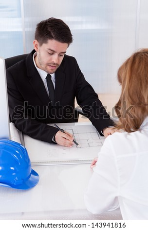 Portrait of two architects discussing blueprints in office - stock photo