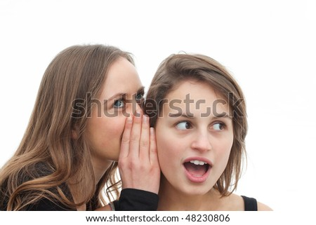 Portrait of two attractive girls gossiping isolated on white background