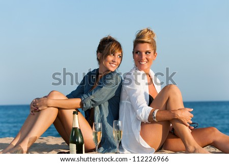 Portrait of two attractive girls sitting back to back on beach.