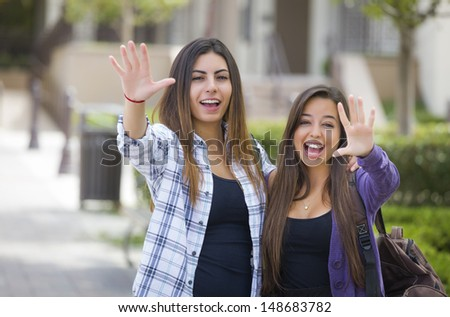 Portrait of Two Attractive Mixed Race Female Students Waving and Carrying Backpacks on School Campus. - stock photo