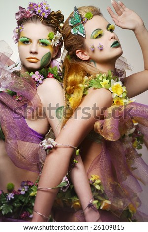 Portrait of two beautiful fashion models wearing costumes made of flowers. - stock photo