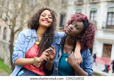 Portrait of two beautiful girls in urban backgrund, black and mixed women. Friends talking - stock photo