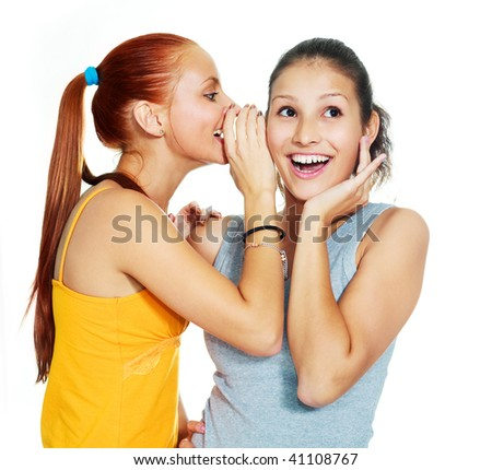 portrait of two beautiful gossiping girls against white background - stock photo