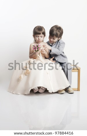 Portrait of two beautiful little boys and girls in wedding dresses from the bridal bouquet on white background - stock photo