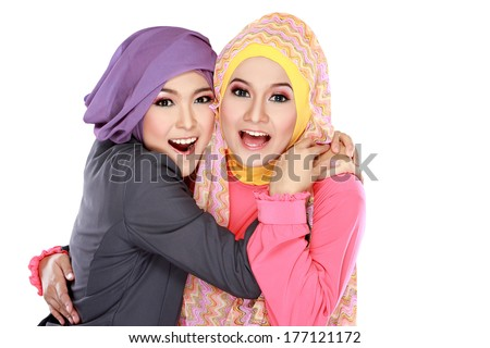 Portrait of two beautiful moslem woman having fun together isolated over white background - stock photo