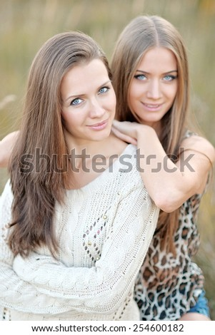 portrait of two beautiful sisters in the autumn