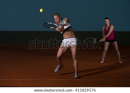 Portrait Of Two Beautiful Women Playing Tennis Indoor - Isolated On Black - stock photo