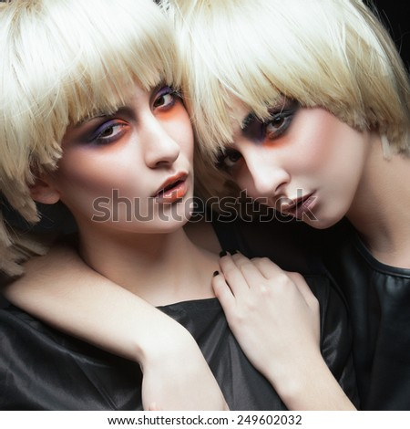 Portrait of two beautiful young girls twins blonde in the studio on a black background, the concept of beauty - stock photo