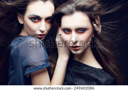 Portrait of two beautiful young girls twins in the studio on a black background, the concept of beauty