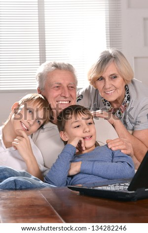 Portrait of two boys and grandparents with a laptop at home