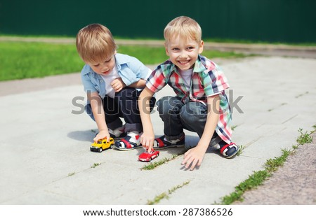Portrait of two boys children playing together with toys outdoors in sunny summer day - stock photo