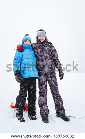 Portrait of two boys, friends, standing on snowy hill. Winter holidays concept. Full height shot. - stock photo