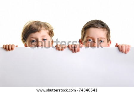 Portrait of two boys holding blank billboard or large white sheet of paper - stock photo