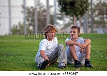 Portrait of two boys on the grass in the park  .