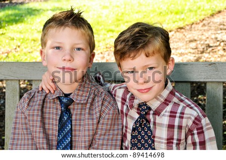 Portrait of two boys, siblings, brothers and best friends smiling. - stock photo