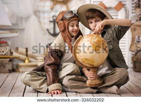 Portrait of two boys - traveler and pilot - with globe in his playroom - stock photo