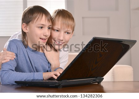 Portrait of two boys with a laptop at home