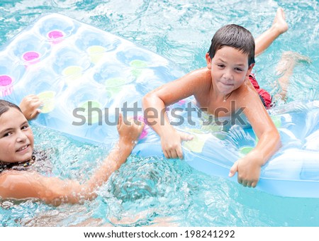 Portrait of two brother and sister children swimming together in a blue pool and sharing an inflatable lilo while enjoying a summer holiday in the sun. Active children and family vacation lifestyle. - stock photo