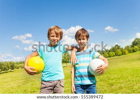 Portrait of two brothers boys stand with holding balls standing in the park on sunny summer day  - stock photo