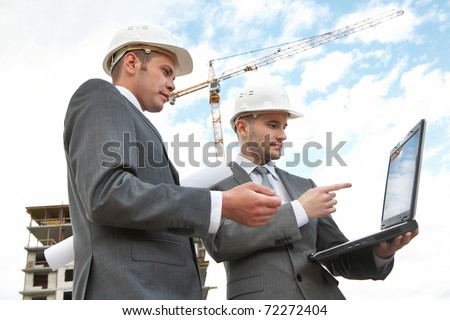 Portrait of two builders standing at building site and looking at laptop display - stock photo