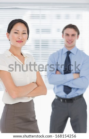 Portrait of two business colleagues standing with arms crossed in the office
