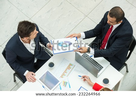 Portrait of two business men are discussing papers at meeting. - stock photo