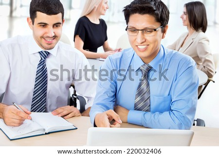 Portrait of two business men with colleagues behind them - stock photo