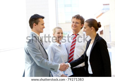 Portrait of two business partners handshaking after making agreement with two employees near by - stock photo