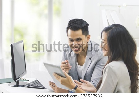 portrait of two business people talk about business at the office and using tablet pc
