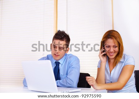 Portrait of two business people working with a laptop.