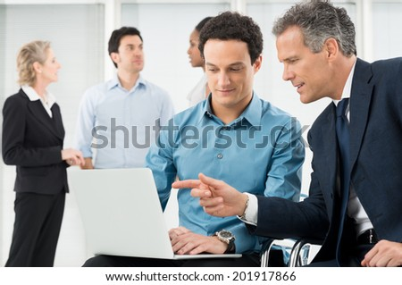 Portrait Of Two Businessman Using Laptop In Office