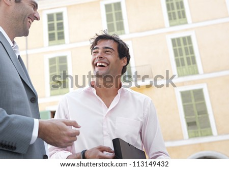Portrait of two businessmen having a conversation while standing next to a classic building in the city, laughing. - stock photo